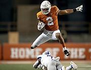 Texas running back Roschon Johnson (2) hurdles over Kansas safety Davon Ferguson (7) during an NCAA football game on Saturday, Oct. 19, 2019, in Austin, Texas. [NICK WAGNER/AMERICAN-STATESMAN]