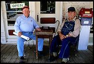 Two men sit outside shop on boardwalk beside wooden checkerboard table in Missouri River town of Arrow Rock, Missouri