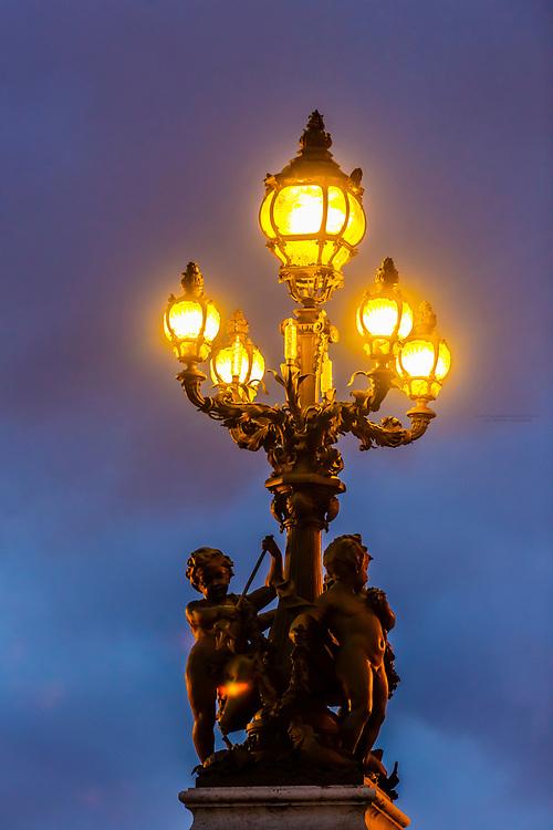 Art nouveau lamps adorned with cherubs, Pont Alexandre III (bridge). It is the most ornate bridge in Paris. Paris, France.