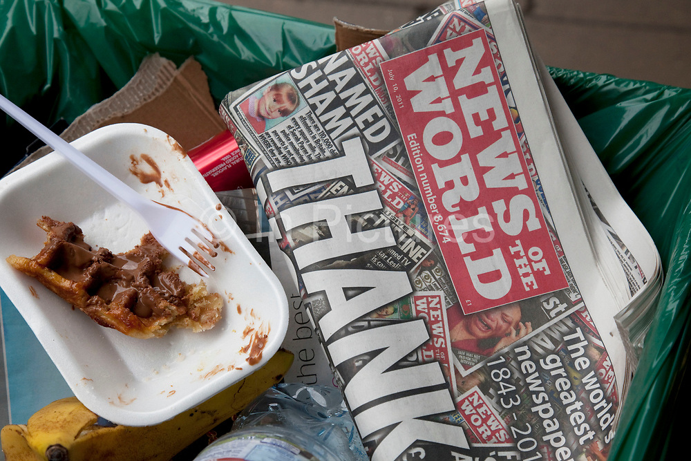 """The last ever copy of tabliod newspaper News of The World in the cart of a street cleaner as someone throws in more rubbish. Sunday 10th July 2011 saw the end for this most famous of newspapers. Embroiled in the phone hacking scandal, this News International paper had approximately 7 million readers at the time of it's demise. On the cover of this, the final edition, with examples of previous journalistic success the headline simply read """"Thank You & Goodbye""""."""