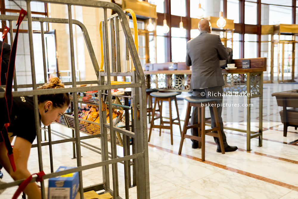 As a cafe worker empties new stock from a wheeled cage, a businessman stands drinking coffee in the City of London, on 21st August 2018, in London, England.