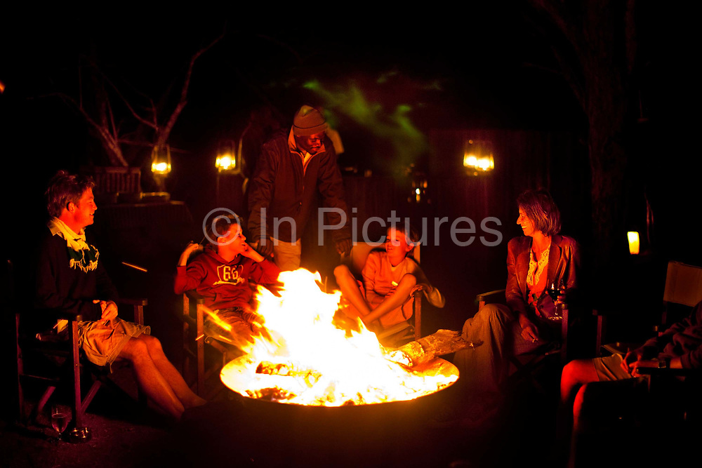 """Horato Clare, Rebecca Shooter with the children Robin Tetlow Shooter & Tyler Talmage sitting around a campfire with Bernard, the tracker, after an evening game drive in the Phinda Game Reserve.<br /> <br /> Phinda Private Game Reserve encompasses an impressive 23 000 hectares (56 800 acres) of prime conservation land wilderness in KwaZulu-Natal, South Africa. Showcasing one of the continent's finest game viewing experiences. Phinda is described as """"Seven Worlds of Wonder"""", with its seven distinct habitats - a magnificent tapestry of woodland, grassland, wetland and forest, interspersed with mountain ranges, river courses, marshes and pans. Phinda is a wilderness sanctuary where intimate encounters, adventure and rare discoveries can be experienced firsthand."""