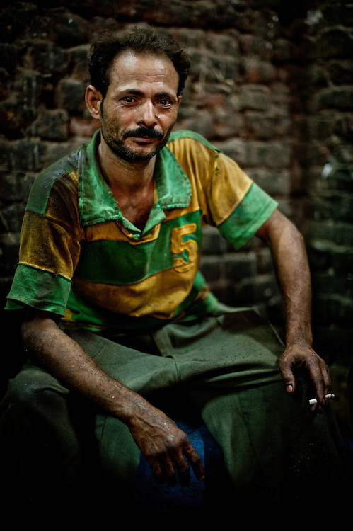 A man takes a break from working at a plastic shredder.