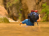 A young man hikes through deep water whle backpacking the Virgin River Narrows in Zion National Park, Utah.