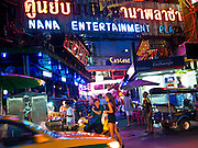 """13 JULY 2011 - BANGKOK, THAILAND:   A man on a motor scooter drops off a woman at the entrance to the Nana Entertainment Plaza, a """"red light"""" district in Bangkok. Prostitution in Thailand is illegal, although in practice it is tolerated and partly regulated. Prostitution is practiced openly throughout the country. The number of prostitutes is difficult to determine, estimates vary widely. Since the Vietnam War, Thailand has gained international notoriety among travelers from many countries as a sex tourism destination. One estimate published in 2003 placed the trade at US$ 4.3 billion per year or about three percent of the Thai economy. It has been suggested that at least 10% of tourist dollars may be spent on the sex trade. According to a 2001 report by the World Health Organisation: """"There are between 150,000 and 200,000 sex workers (in Thailand).""""  PHOTO BY JACK KURTZ"""