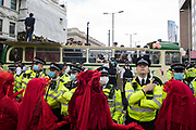 Members of the Red Rebel Brigade circle a vintage bus used by Extinction Rebellion to block a road junction to the south of London Bridge on the ninth day of their Impossible Rebellion protests on 31st August 2021 in London, United Kingdom. Extinction Rebellion are calling on the UK government to cease all new fossil fuel investment with immediate effect.