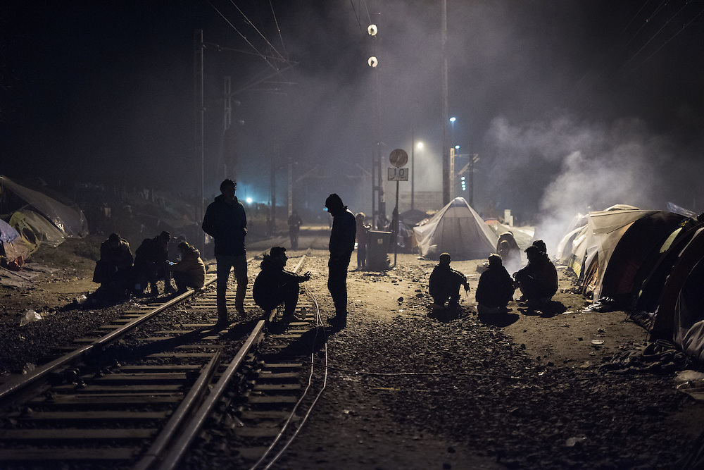 Refugees and migrants sitting by the railway tracks in Idomeni. <br /> <br /> Thousands of refugees are stranded in Idomeni unable to cross the border. The facilities are stretched to the limit and the conditions are appalling.