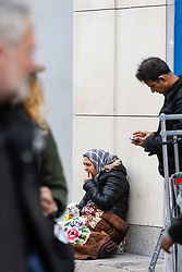 A woman in a headscarf begs on Oxford Street near Bond Street Underground Station. Homeless Britons are coming under increasing pressure as a surge of Roma beggars from Romania arrive on the streets of London to take advantage of the generosity of Christmas shoppers. London, December 04 2018.