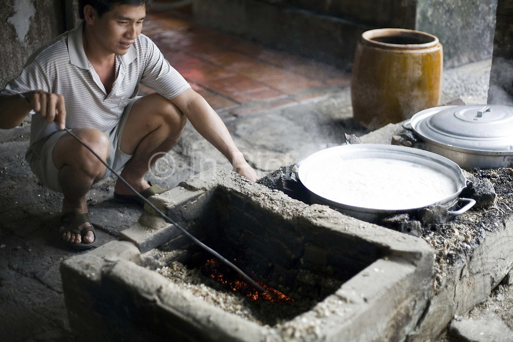 A man boils noodles in the traditional manner in a pot at a family farm, Tay Ninh, Vietnam