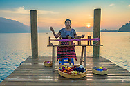 Because the textiles produced by backstrap weaving are smaller, the warper is portable. Here a demonstration of how they warp the yarn. This photo was shot at sunrise over Lake Atitlan.