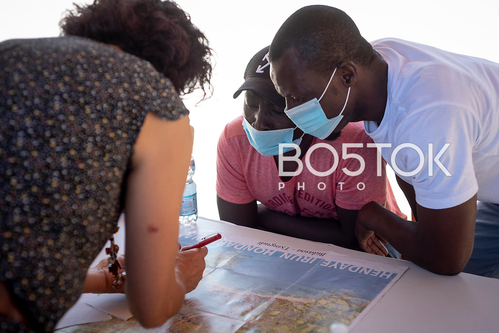 Sub-Saharan migrants who arrived in Irun the night before attend to a volunteer's explanations about the roads to cross the border. Irun (Basque Country). August 6, 2020. A group of volunteers has created a host network to serve migrants and inform about the public services they are entitled to and the ways to cross the border. This group of volunteers is avoiding a serious humanitarian problem Irun, the Basque municipality on the border with Hendaye. As the number of migrants arriving on the coasts of southern Spain incresead, more and more migrants are heading north to the border city of Irun. One of the functions performed by these volunteers is to direct the newcomers to the device the red cross has for migrants in transit, so that they can sleep in a safe place. (Gari Garaialde / Bostok Photo)