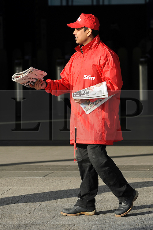 © Licensed to London News Pictures. 26/02/2012, London, UK. A vendor sells the first Sunday edition of the Sun newspaper at Shepherds Bush Tube Station today 26 February 2012. The newspaper is now published 7 days a week. . Photo credit : Stephen Simpson/LNP