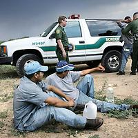 Verenigde Staten.Arizona.Nogales.juli 2005.<br /> Grenspolitie arresteert illegalen in de woestijn van Zuid Arizona, die illegaal vanuit Mexico de Verenigde Staten zijn binnengekomen. Ze worden gefoullerd op wapens en hun papieren worden gecontroleerd. Daarna worden de illegalen naar het hoofdbureau van de grenspolitie getransporteerd, waarna ze geregistreerd worden alvorens ze terug de grens overgebracht worden.Dagelijks proberen duizenden illegalen vanuit Mexico de Verenigde Staten binnen te komen en hopen op een beter leven.Border Patrol.Mexiacanen.Illegale vluchtelingen. Grensproblematiek.woestijn.Body check.Droogte.Water.Mexicanen.<br /> Archives 2005. Chase by police on illegal Mexicans who cross the border in Arizona.