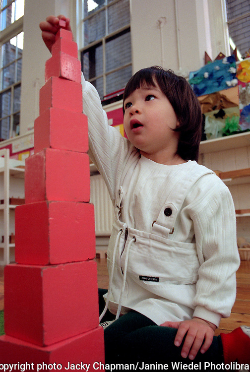 Small boy building the Montessori tower with pink blocks.