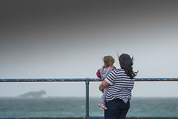 A mother and child look out to sea on a windy day in Newquay.