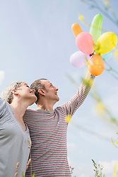 Mature couple with bunch of balloons, smiling