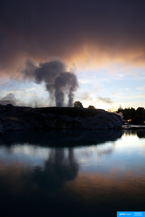 A spectacular geyser at sunset at Te Puia, Rotorua. Te Puia is the premier Maori cultural centre in New Zealand - a place of gushing waters, steaming vents, boiling mud pools and spectacular geysers. Te Puia also hosts National Carving and Weaving Schools and  daily maori culture performances including dancing and singing. Rotorua, 9th December 2010 New Zealand.  Photo Tim Clayton