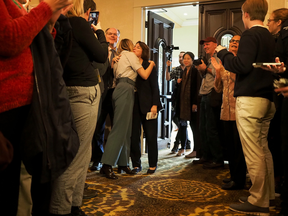Amy Klobuchar greets her daughter, Abigail Klobuchar Bessler, as her husband John Bessler and supporters look on at the Cedar Rapids Get Out the Caucus Rally