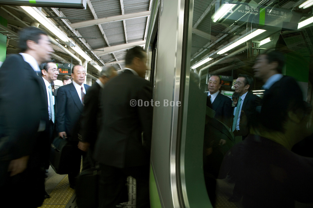 Japanese business people entering a commuter train