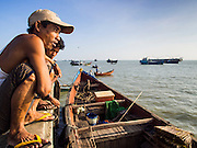10 NOVEMBER 2014 - SITTWE, MYANMAR:  Men sit on the end of the municipal pier in Sittwe, Myanmar. Sittwe is a small town in the Myanmar state of Rakhine, on the Bay of Bengal.   PHOTO BY JACK KURTZ