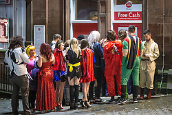 © Licensed to London News Pictures . 26/12/2015 . Wigan , UK . People queue at a cashpoint . Revellers in Wigan enjoy Boxing Day drinks and clubbing in Wigan Wallgate . In recent years a tradition has been established in which put on fancy dress for a Boxing Day night out . Photo credit : Joel Goodman/LNP