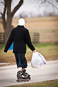 Amish girl roller blades home from school in Gordonville, PA.