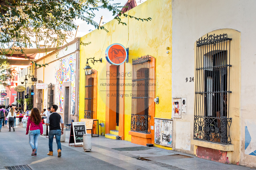 People walk past brightly painted Spanish colonial style buildings in the Barrio Antiguo or Spanish Quarter neighborhood adjacent to the Macroplaza Grand Plaza in Monterrey, Nuevo Leon, Mexico.