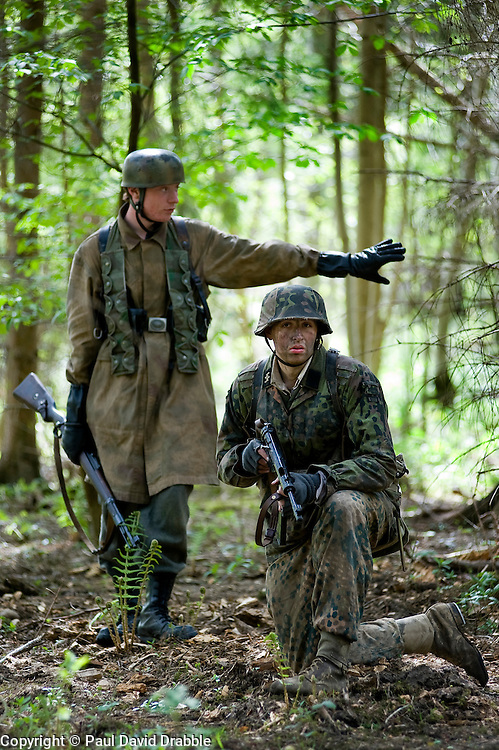 Living History Reenactors a Fallschirmjaeger (German Paratrooper) carrying a Mauser k98 rifle  and a  Waffen SS soldier weraing Pea Dot and Oakleaf camouflage with an MP40 Sub machine gun in a Woodland setting. <br /> Images © Paul David Drabble.