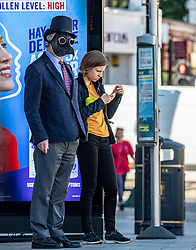 © Licensed to London News Pictures. 15/06/2020. London, UK. A man in a Doctor's plague mask waits for a bus in Putney, South London as commuters are told to wear masks from Monday while travelling on Public Transport. Also non essential shops are given the green light to open in England after 3 months of being closed due to the coronavirus pandemic. Photo credit: Alex Lentati/LNP