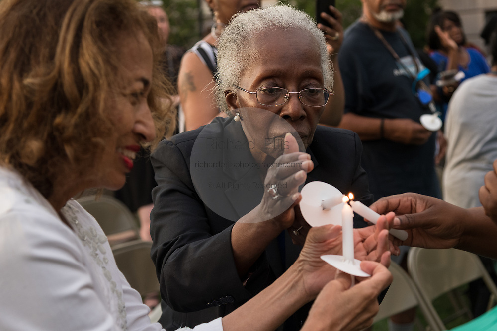 Relatives and friends of the Emanuel 9, killed in a mass shooting at the historic Mother Emanuel African Methodist Episcopal Church, light candles during the Pray for America service marking the 4th anniversary of the mass shooting June 19, 2019 in Charleston, South Carolina. Nine members of the historically black congregation were gunned down during bible study by a white supremacist on June 17, 2015.