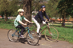 Mother and son wearing cycle helmets riding bicycles through park,