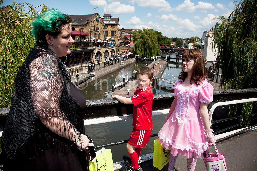 Mother Louise Irwin-Ryan with her daughter Georgia (11, wearing a pink Lolita dress) and son Kiefer (8, wearing a red Liverpool Football Club kit) spending a day out together in Camden Town, North London. At the end of their day they walk across the famous bridge at Camden Lock in the summer sunshine. Louise is on various benefits to help support her family income, and housing, although recent government changes to benefits may affect her family drastically, possibly meaning they may have to move out of London. Louise Ryan was born on the Wirral peninsula in 1970.  She moved to London with her family in 1980.  Having lived in both Manchester and Ireland, she now lives permanently in North London with her husband and two children. Through the years Louise has battled to recover from a serious motorcycle accident in 1992 and has recently been diagnosed with Bipolar Affective Disorder. (Photo by Mike Kemp/For The Washington Post)