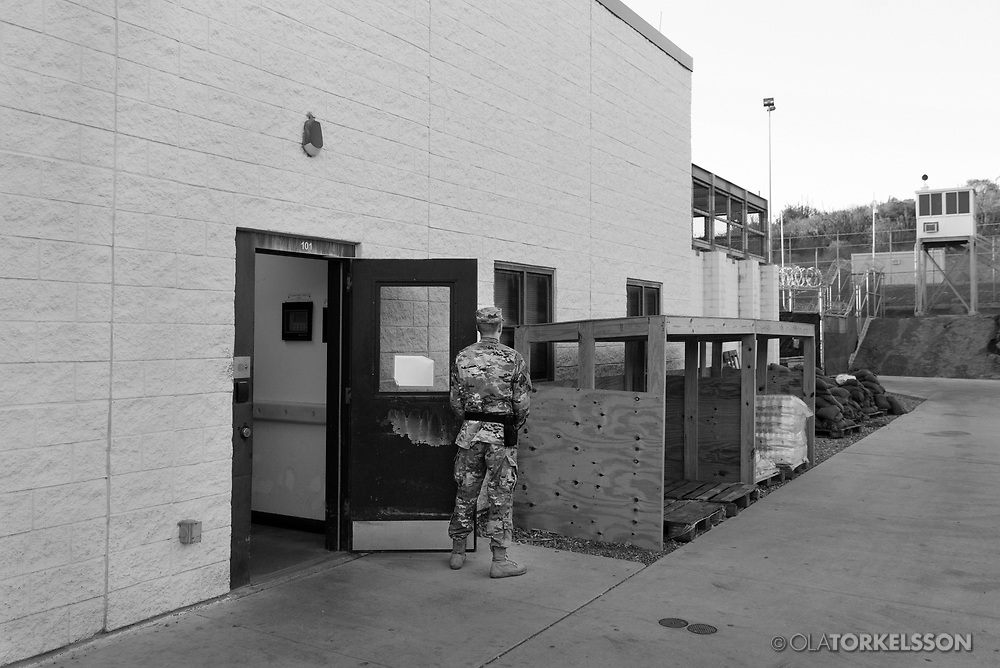 """A military guard at the prison camp at Guantanamo, Cuba, Jan 28 2017, guards a door to a prison building.<br /> The guards turn away their faces so you cannot identify them. It is standard operation procedure when pictures are made. When you work as a journalist at the Guantanamo you work under military censorship and all your material is checked every day and approved for publication.<br /> The prison camp on the Guantánamo naval base was the creation of President George W. Bush. The prison camp was considered an important part of the US war on terrorism. Over the years, 779 people have been brought to the camp. 41 people are still detained. Of them, 26 people count as """"forever prisoners"""", indefinite detainees under the Law of War. Two prisoners have been in the camp since it was opened in January 2002. The last prisoner taken to the camp came in March 2008. The so-called war on Terror and the Guantanamo prison camp have been heavily criticized for violation of human rights regarding torture and habeas corpus.<br /> It is unclear what US President Donald Trump wants to do with the camp, but during the election campaign he said that he would fill Guantánamo Bay with """"bad dudes"""". Photo by Ola Torkelsson<br /> Copyright Ola Torkelsson ©"""
