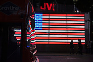 In Times Square, electric American Flag with its reflection on bus passing by, with bus driver seen in silhouette, in Manhattan, New York City, New York, USA, on January 9, 2012