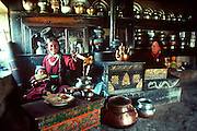 INDIA, LADAKH Ladakhi women and child preparing tea  surrounded by traditional stove and pots  in their kitchen in Leh