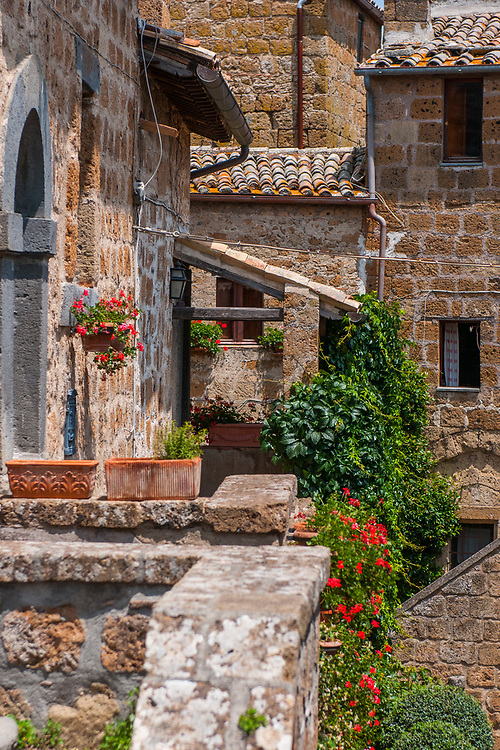 """A view of houses of the village of Civita di Bagnoregio.<br /> Civita di Bagnoregio is a town in the Province of Viterbo in central Italy, a suburb of the comune of Bagnoregio, 1 kilometre (0.6 mi) east from it. It is about 120 kilometres (75 mi) north of Rome. Civita was founded by Etruscans more than 2,500 years ago. Bagnoregio continues as a small but prosperous town, while Civita became known in Italian as La città che muore (""""The Dying Town""""). Civita has only recently been experiencing a tourist revival. The population today varies from about 7 people in winter to more than 100 in summer.The town was placed on the World Monuments Fund's 2006 Watch List of the 100 Most Endangered Sites, because of threats it faces from erosion and unregulated tourism."""