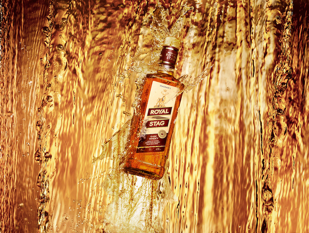 Bottle in a waterfall of of Whisky Ray Massey is an established, award winning, UK professional  photographer, shooting creative advertising and editorial images from his stunning studio in a converted church in Camden Town, London NW1. Ray Massey specialises in drinks and liquids, still life and hands, product, gymnastics, special effects (sfx) and location photography. He is particularly known for dynamic high speed action shots of pours, bubbles, splashes and explosions in beers, champagnes, sodas, cocktails and beverages of all descriptions, as well as perfumes, paint, ink, water – even ice! Ray Massey works throughout the world with advertising agencies, designers, design groups, PR companies and directly with clients. He regularly manages the entire creative process, including post-production composition, manipulation and retouching, working with his team of retouchers to produce final images ready for publication.