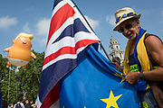 The inflatable balloon called Baby Trump flies above a Brexit protestor and the British Union Jack flag Parliament Square in Westminster, the seat of the UK Parliament, during the US Presidents visit to the UK, on 13th July 2018, in London, England. Baby Trump is a 20ft high orange blimp depicting the US President as an enraged, smartphone-clutching infant - and given special permission to appear above the capital by London Mayor Sadiq Khan because of its protest rather than artistic nature. It is the brainchild of Graphic designer Matt Bonner.