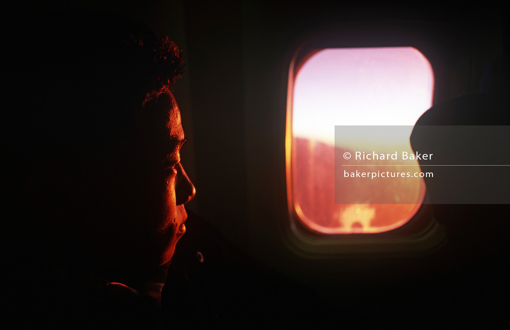 A newly-recruited Nepali boy stares through the window of a Nepal Airlines airliner during his flight from his Himalayan homeland to the UK where his 2-year training for the British Army will begin, on 16th January 1997, in Kathmandu, Nepal. He is leaving behind his family for England where the British army is to make him a fully-trained soldier in the Gurkha Regiment. Some 60,000 young Nepalese boys aged between 17 - 22 (or 25 for those educated enough to become clerks or communications specialists) report to designated recruiting stations in the hills each November, most living from altitudes ranging from 4,000 - 12,000 feet. After initial selection, 7,000 are accepted for further tests from which 700 are sent down here to Pokhara in the shadow of the Himalayas. Only 160 of the best boys succeed in the flight to the UK. The Gurkhas training wing in Nepal has been supplying youth for the British army since the Indian Mutiny of 1857. (Photo by Richard Baker / In Pictures via Getty Images)