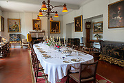 Dining room inside Berkeley castle, Gloucestershire, England, UK with table laid for dinner