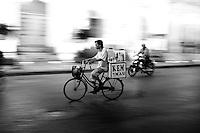 An icecream vendor cycling around the streets of Saigon at night.