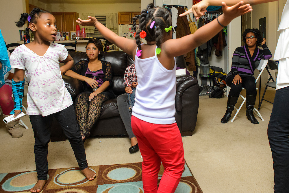 Photo by Matt Roth..An argument centered around video game play unfolds between the Mcnair Sisters Leah, 6, Lana, 5, and Kayla, 13, after Thanksgiving dinner at their house in Sewell, New Jersey on Thursday, November 22, 2012. Watching the dispute unfold are Martela Stewart, left, and Melissa Boone Brown, right. Melissa, a first generation doctoral student in the Department of Sociomedical Sciences at Columbia University spends the Thanksgiving holidays with her cousin who lives next door. Her parents are Jehovahs Witnesses who live in Atlanta...Tensions, misunderstandings, and awkwardness that can sometimes arise when a first generation college student comes home for the holidays..
