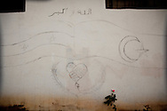 The flags of Syrian and Turkey are drawn on a wall in Antakya southern Turkey, under the words 'AllahuAkbar' (God is great). 12/06/2012