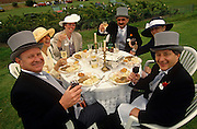 In the middle of a field serving as a grass car park, three couples celebrate the Ladies' Day event at Royal Ascot. Holding their glasses to toast a grand day out at this annual sporting event in the social calendar, the gentlemen are dressed in formal top hats and tails, the ladies in wide hats and summer dresses. Grinning and looking smug in their upp-class social status, they are seated eccentrically and comically around a plastic table with a tablecloth, two Candelabras and their picnic lunch plates full of fine food.