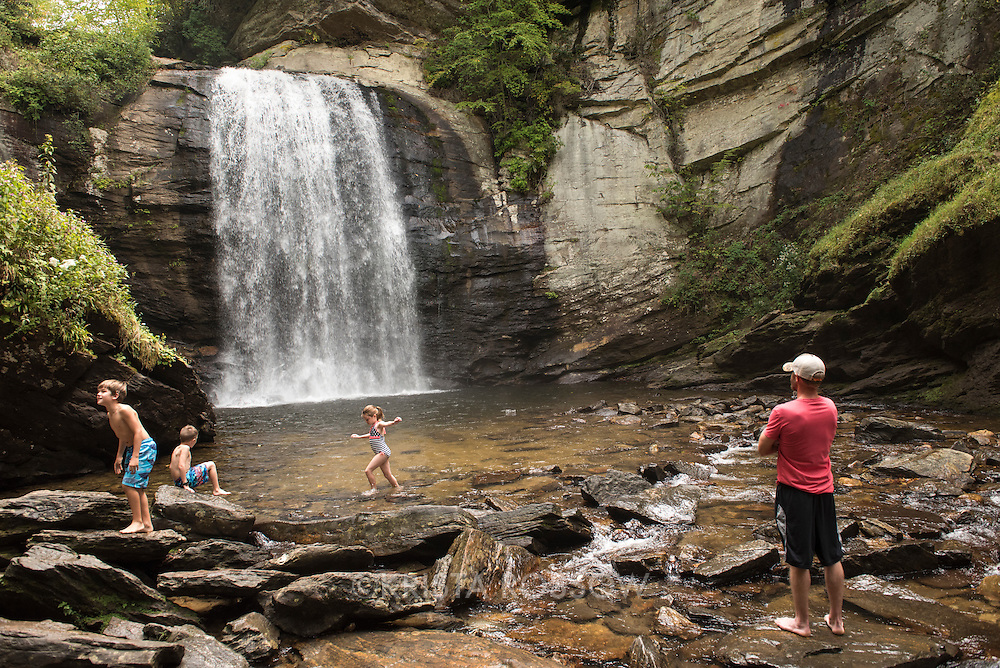 A family plays in the water at Looking Glass Falls , a popular waterfall and swimming hole in the Pisgah National Forest located near Brevard, North Carolina, southwest of Asheville and about 10 miles off of the Blue Ridge Parkway.