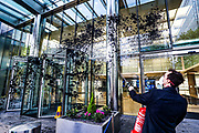 One of three members of the Extinction Rebellion environmental activist group is seen spraying a dark colour at Barclays HQ building in Canary Wharf on Thursday, May 7, 2020. Barclays is the biggest European financier of fossil fuel companies. (Photo/ Vudi Xhymshiti)