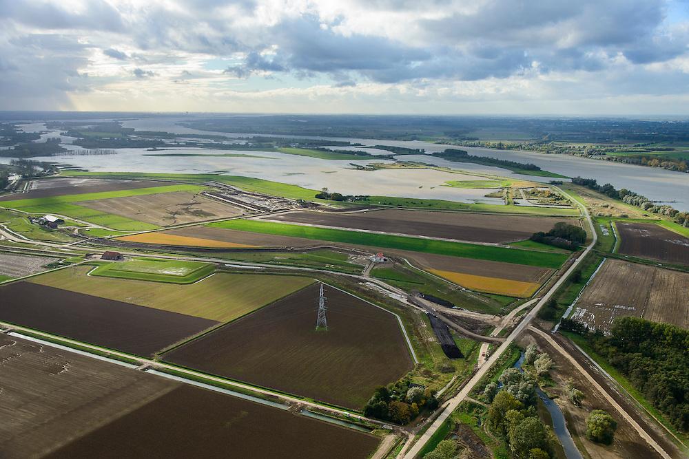 Nederland, Noord-Brabant, Werkendam, 23-10-2013; Ruimte voor de Rivier project Ontpoldering Noordwaard. Het deel boven is reeds ontpolderd, onder het gedeelte in ontwikkeling waar boerderijen en particuliere huizen op nieuw opgeworpen terpen gebouwd worden. Diagonaal in beeld een nieuwe dijk, hierlangs zal het water stromen, vanaf rivier de Nieuwe Merwede (rechts).<br /> Delen van de polder wordt ontpolderd en de dijken worden verlegd en/of verlaad waardoor bij hoogwater het rivierwater ook door de polder sneller weg kan stromen richting zee. Gevolg van de ingrepen is ook dat de waterstand verder stroomopwaarts zal dalen.<br /> National Project Ruimte voor de Rivier (Room for the River) By lowering and / or moving the dike of the Noordwaard polder the area will become subject to controlled inundation and function as a dedicated water detention district. Houses and farmhouses will be constructed on new dwelling mounds. The polder is partly depoldered.<br /> luchtfoto (toeslag op standard tarieven);<br /> aerial photo (additional fee required);<br /> copyright foto/photo Siebe Swart