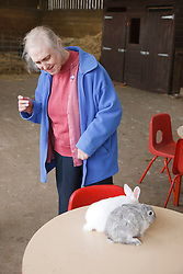 Woman with learning disability on trip to farm looking at rabbits