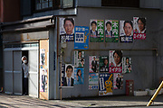 An older Japanese man looks out of a building with many political posters on its side. Ueno, Tokyo, Japan. Friday March 19th 2021