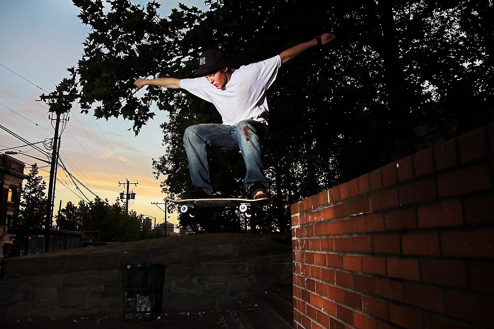 Trevor Fenner jumps off of a brick ledge with his skateboard near the entrance to Seattle University in Seattle, Washington.